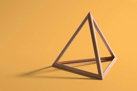 Open empty wooden triangular frame or pyramid shape forming a standard geometric triangle casting a shadow on a yellow background