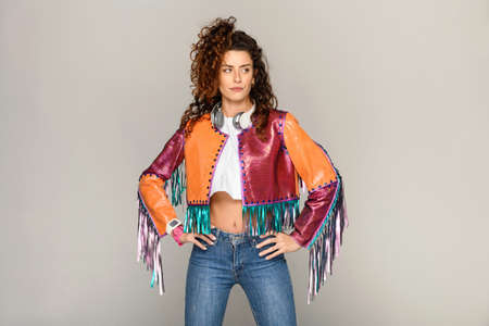 Trendy bohemian young woman in multicolored jacket with tassel fringe standing akimbo with hands an hips over a light grey studio background