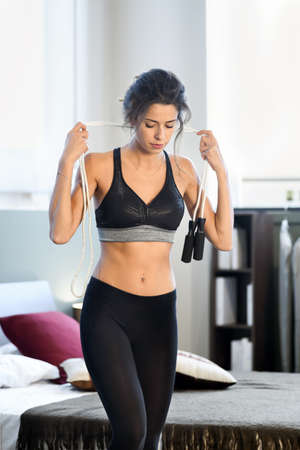 Young sportive woman in black tight sportswear standing in bedroom at home with skipping rope in her hands, and looking down