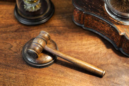 Small wooden judges gavel on a desk in a high angle view conceptual of crime, law and order, sentencing, court or an auction