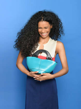 Candid portrait of a lovely laughing black woman with long curly hair holding a leather bag to her chest over a blue background Imagens