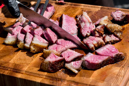Chef slicing tender medium rare roast beef brisket with a large carving knife in a close up view on the chopping board