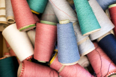 Full frame background texture of assorted colors of cashmere wool or yarn on spools in a random juble viewed from above