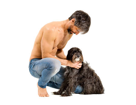 Fit athletic shirtless man in his 50s bending down caressing his pet dog on a white studio background