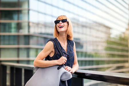 Vivacious trendy woman in modern sunglasses standing against the railing of a walkway in a city laughing happily as she looks up to the sky with glass skyscraper backdrop