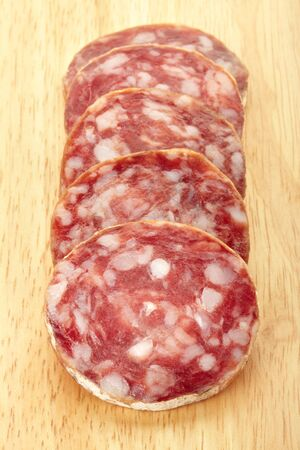 Sliced salami on cutting board photo