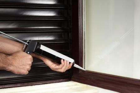 glue: Anwenden von Silikon-Dichtstoff mit Kartuschenpistole Lizenzfreie Bilder