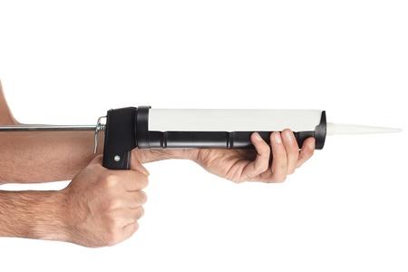 Applying silicone with caulking gun on white