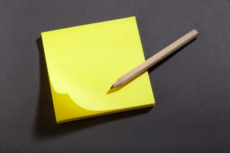 Yellow sticker block note on blackboard and pencil Stock Photo - 16672870