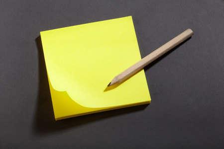 block note: Yellow sticker block note on blackboard and pencil