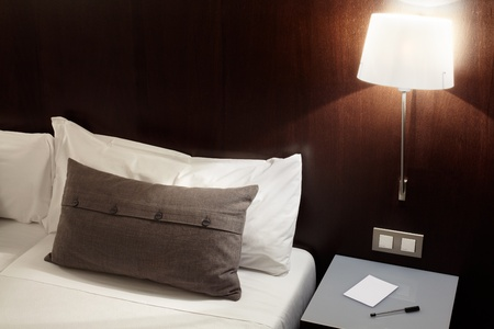 Modern bedroom, pillow and lamp at night photo