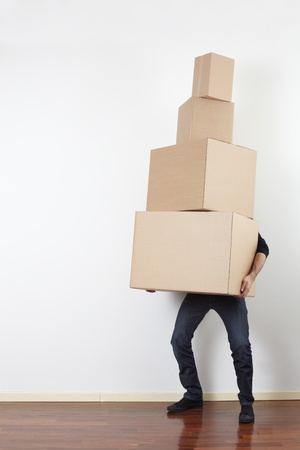Man lifting cardboard boxes in apartment Stock Photo