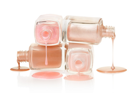 Pink nail polish bottles spilling on white, clipping path