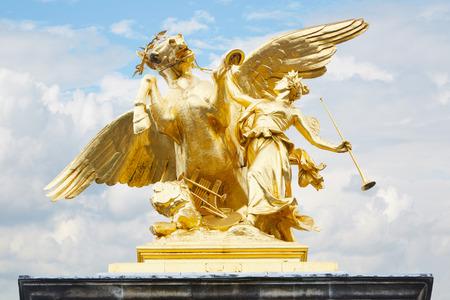 Alexandre III bridge golden statue in Paris, France photo