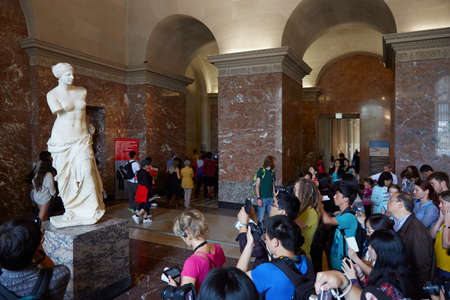 Venus of Milo statue with tourists in Louvre museum, Paris
