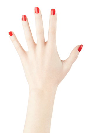 manicured: Red nail polish on woman hand raised up on white
