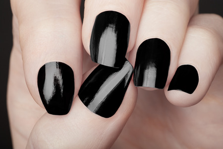 Manicure on female hand with black nail polish close up