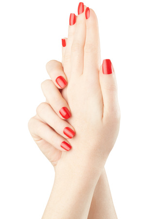 Manicure on female hands with red nail polish on white, clipping path