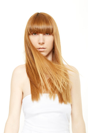 beautiful bangs: Blond hair. Young woman with long, straight hair in wind with fringe on white, clipping path