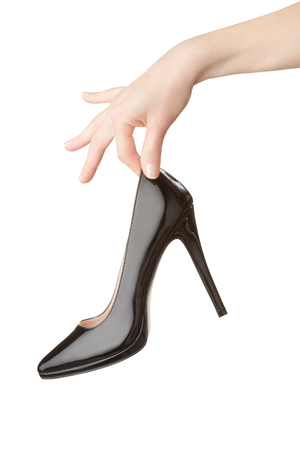patent leather: Woman hand holding black high heel shoe on white, clipping path Stock Photo
