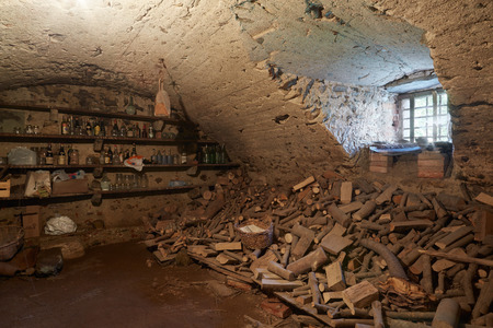 basement: Old, dark basement with wood pile in ancient house