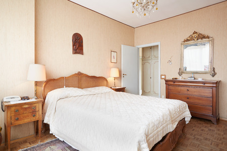 house with style: Old bedroom with queen size bed in ancient house Stock Photo