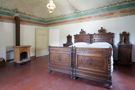 queen bed: Wooden bedroom in ancient house with floral frescos