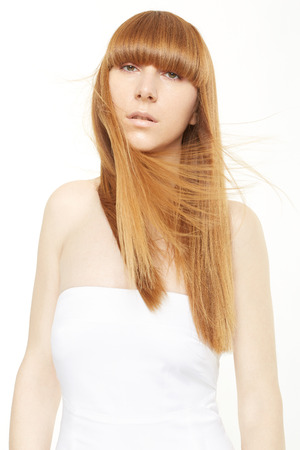 long straight hair: Young woman with blond, long, straight hair in wind on white