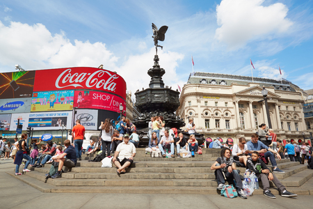 piccadilly: Piccadilly Circus Eros fountain with people and neon signage in London Editorial