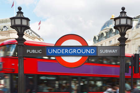 street signs: London underground sign with street lamps and red double decker bus background