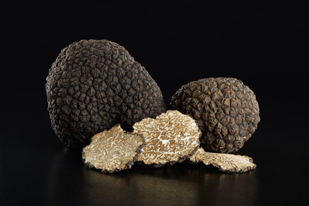Black truffles and slices on black, clipping path