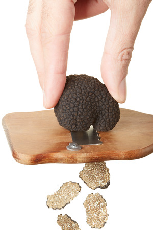truffe blanche: Hand slicing black truffle with wooden truffle slicer on white, clipping path Banque d'images