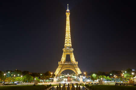illuminate: Eiffel tower with golden illumination by night in Paris Editorial