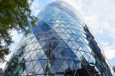 30 st mary axe: LONDON - AUGUST 9, 2015: 30 St Mary Axe building or Gherkin in the morning with tree on August 9, 2015 in London. The skyscraper designed by architect Norman Foster is one of citys most widely recognized examples of contemporary architecture