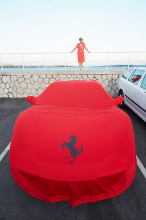 red cloth: Ferrari red cloth cover at the harbor with woman in Cannes, France. Ferrari emblem is the rampant horse.