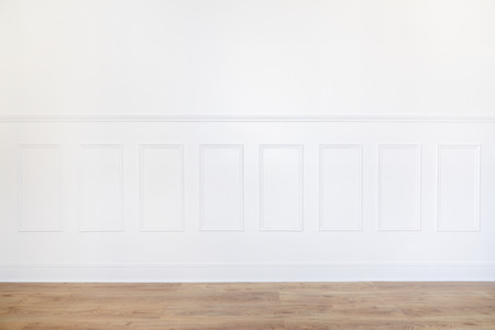 Empty white room with parquet floor and wood trimmed wall Standard-Bild