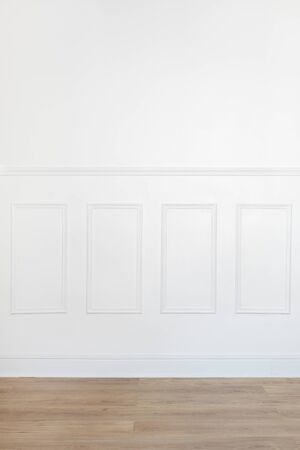 trim wall: Empty white room with parquet floor and wood trimmed wall Stock Photo
