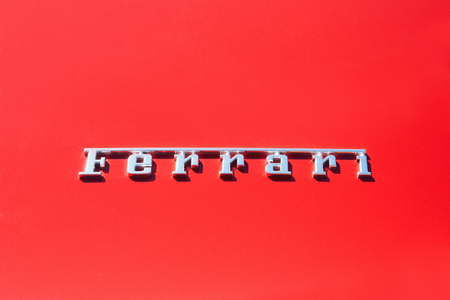 ferrari: Silver Ferrari logo on red metal car body in Paris