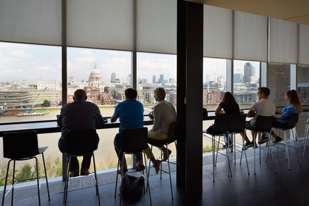 sitting people: Tate Modern Art Gallery cafe interior with people and city view in London Editorial