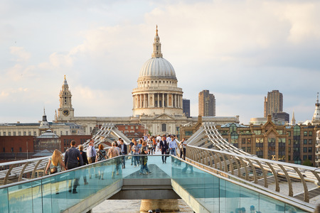 Millennium bridge with people walking and St Paul cathedral in the afternoon in London Editorial