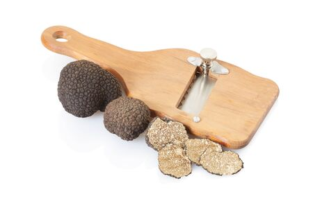 Black truffle, slices and wooden truffle slicer on white, clipping path