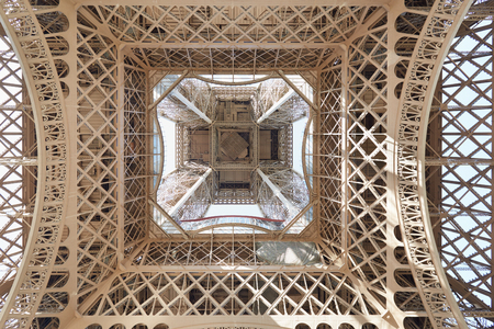 underneath: Eiffel tower structure under view in Paris, sunny day