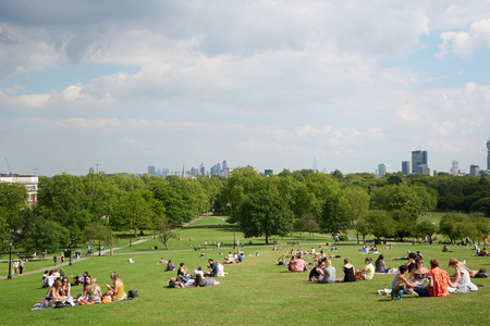 Primrose hill top with London city view and people relaxing in the park in London