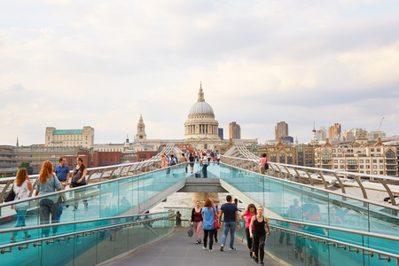 Millennium bridge with people walking and St Paul cathedral in a summer evening in London