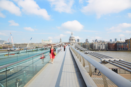millennium bridge: Millennium bridge with people walking and St Paul cathedral in a sunny morning in London