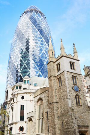 30 st mary axe: St. Andrew Undershaft Church with 30 St. Mary Axe above in a sunny day  in London