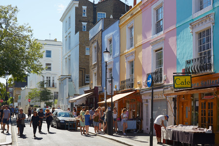 notting: Portobello road with colorful houses and people walking in a sunny day in London