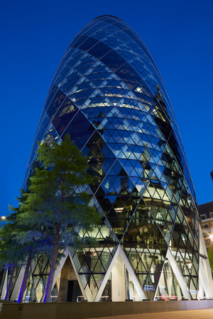 gherkin: 30 St Mary Axe building or Gherkin illuminated at night in London Editorial