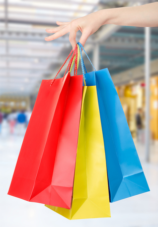 shopping mall: Woman hand holding shopping bags with shopping mall background