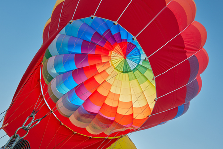 Hot air balloon, colorful aerostat inflating, blue sky